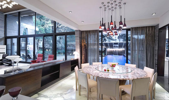 Dining room celebrates connection with pool and the voluminous living space