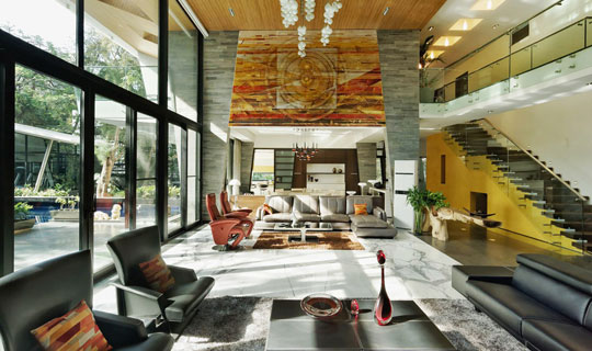 Double height living room invites nature in through glazed walls